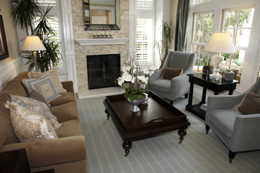 An elegant living room with a light fireplace with a multi-tonal stone facade. The fireplace is screened in so that coals or sparks will not set the light blue carpet alight.