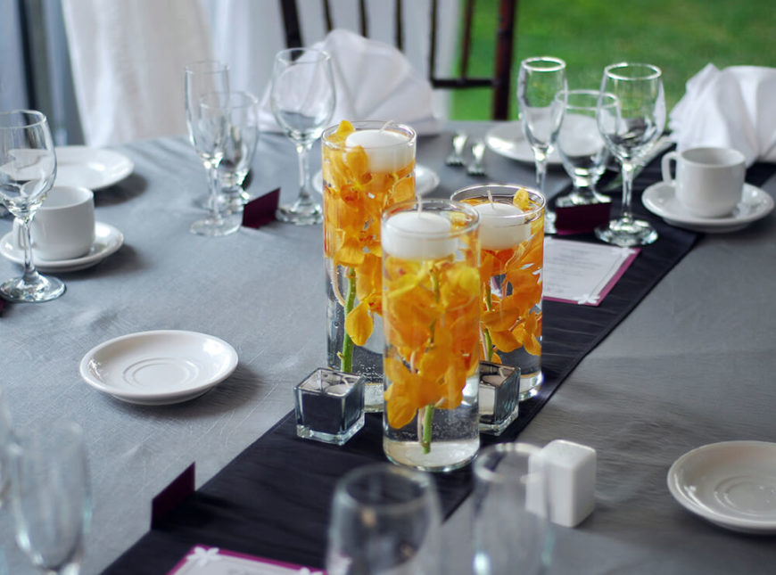 Bold yellow orchids are suspended in water in a tall glass vase. At the top are floating candles.
