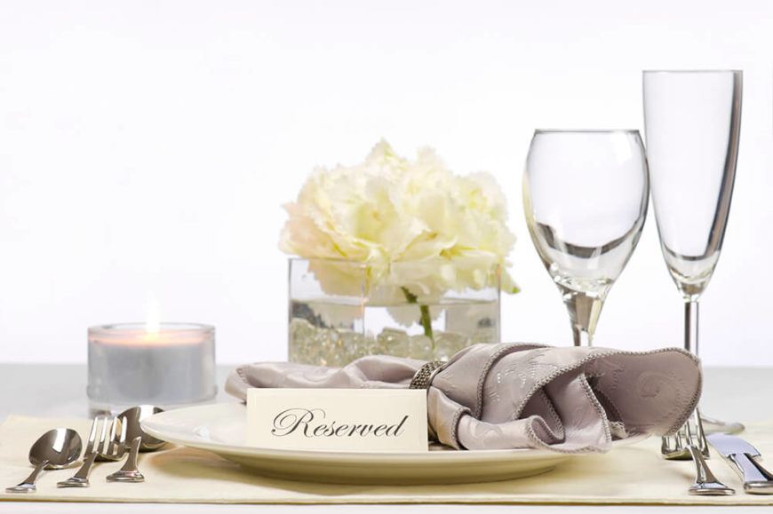 A beautiful silver and white wedding place setting with a lovely floral centerpiece and a candle behind the plate.
