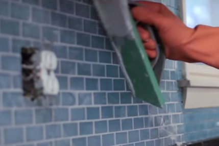 Press the grout into the joints using the rubber float. Use the edge of the float to sweep away any excess grout. Do this at a 45° angle.