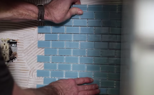Take your tile sheets and press into the wet adhesive from the bottom up.