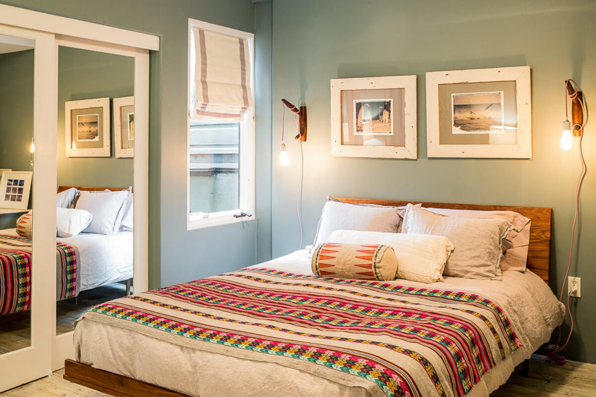 The room also includes a mirrored closet, but perhaps the best feature is the colorful bedding. On either side of the bed are industrial wall sconces.