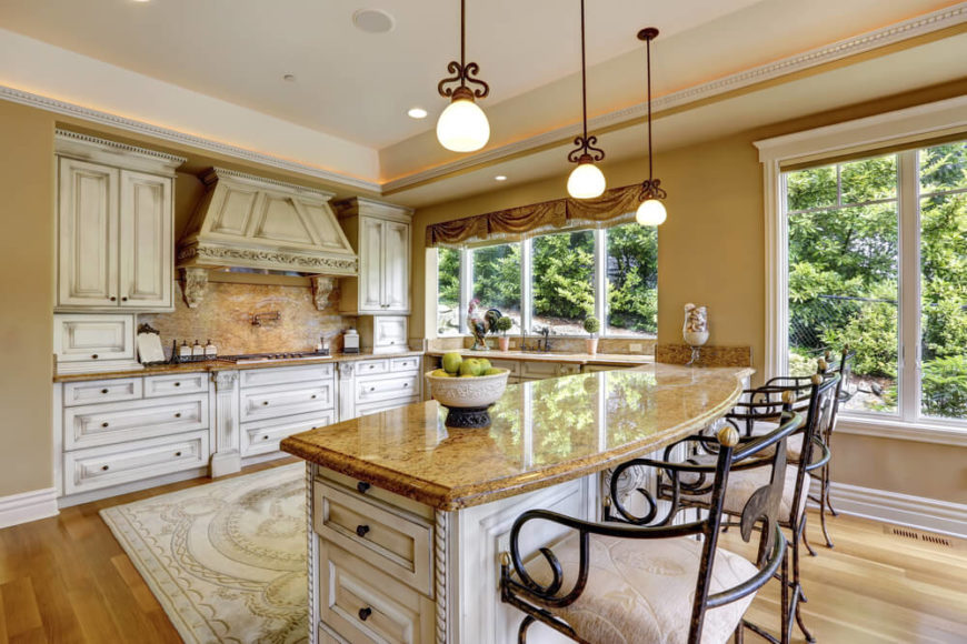 The same kitchen from a different angle shows off the amazing details on the vent hood and the meal preparation area. Beautiful roman curtains accent the large windows for the perfect touch of country style.
