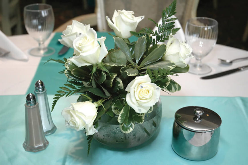 A small and delicate floral arrangement consisting of white roses tucked into a glass vase with ivy and ferns. This smaller centerpiece is perfect for any occasion, from a wedding reception to a formal date night dinner.