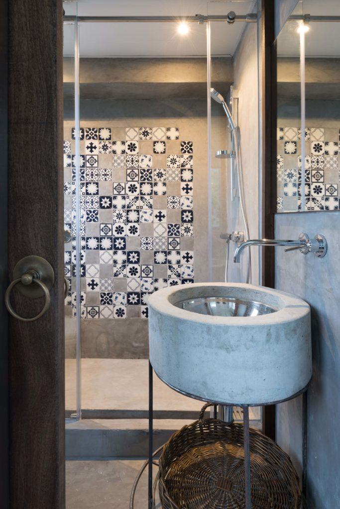 Here we see the shower space, which showcases an intricate display of tilework. The sink basin is encased in concrete, fitting the aesthetic of the room.