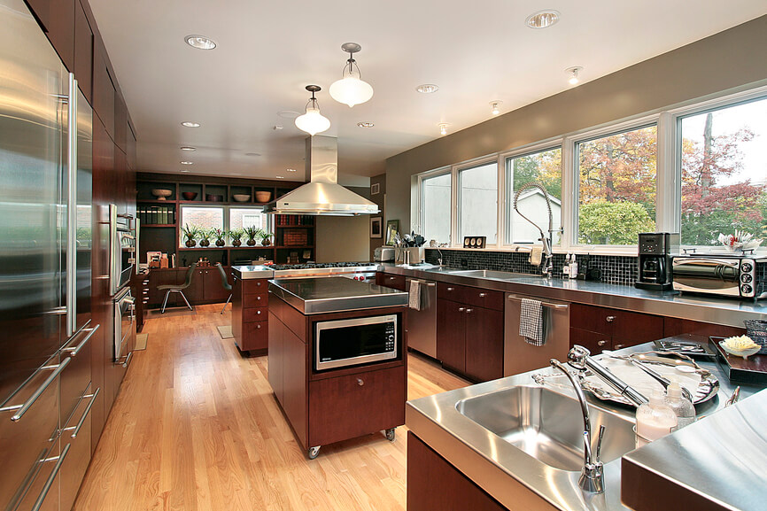 This contemporary kitchen has picture windows lining the kitchen counter tops. Beautiful light enters through the windows and creates a wonderful shine to this metallic and hardwood design.