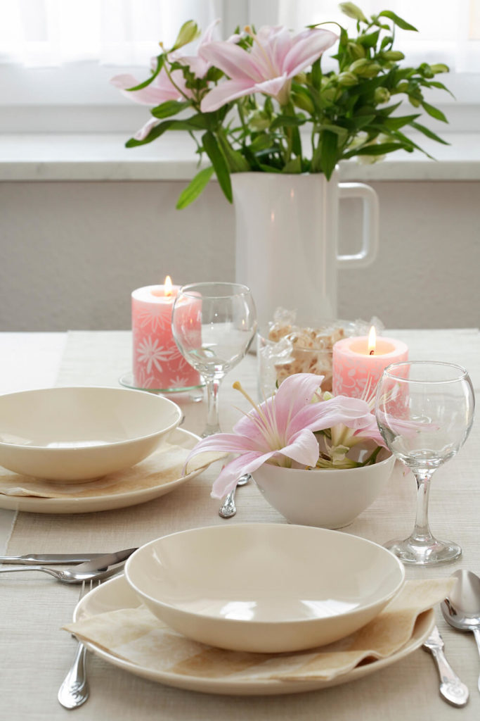 A much more simple floral centerpiece, with two lily blooms in a small bowl next to a pink candle.