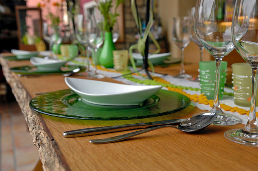 A wide green-tinted glass dinner plate is topped by a long, thin soup bowl. To the right are two large wine glasses, above the utensils.