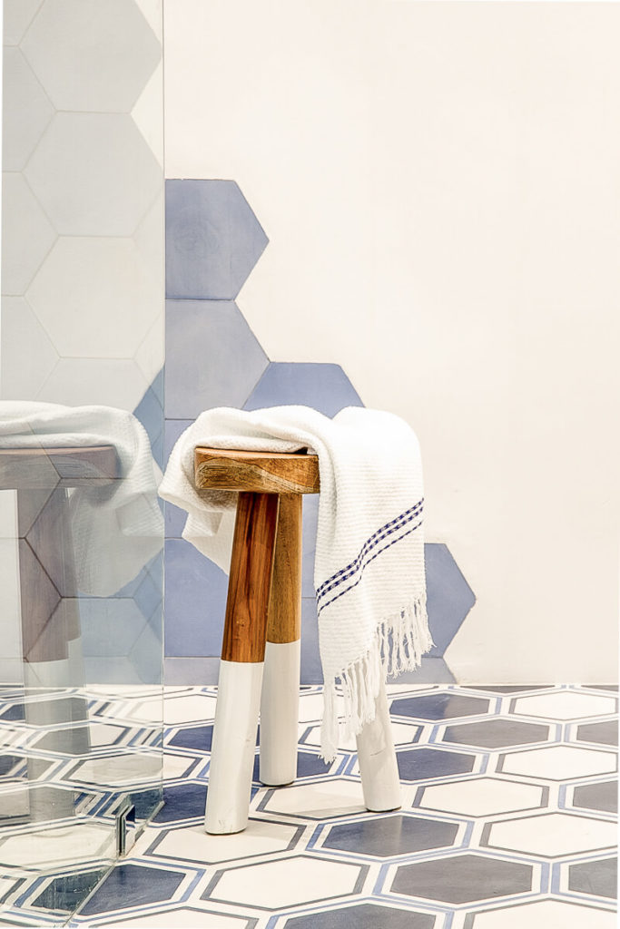 A simple wooden stool adds an organic element to this entirely modern primary bathroom.