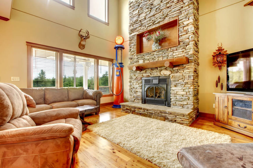 An eclectic living room with a plush white rug and an enormous stone fireplace that extends from the wall. An antique gas pumps sits in one corner of the room, a cuckoo clock in another.