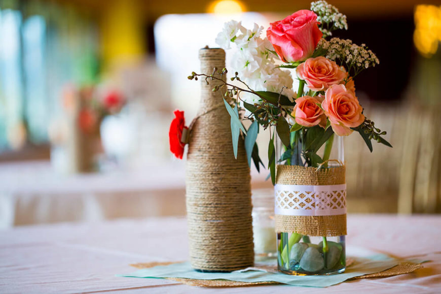 Embracing the burlap trend is this glass vase wrapped in burlap and a paper doily, filled with roses and baby's breath.