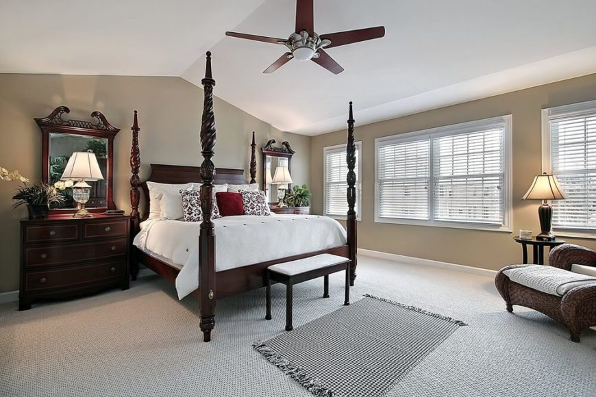 The ceiling of this primary bedroom is arched at the center and slopes to flat above the large windows. The furniture is a beautiful dark cherry with carved posts.
