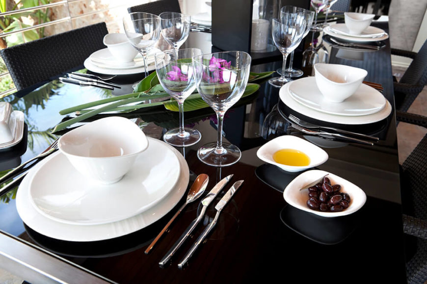 The white dishes against the glossy black table are stunning. The curved shape of the dishes and wine glasses add another unique cast to this table.