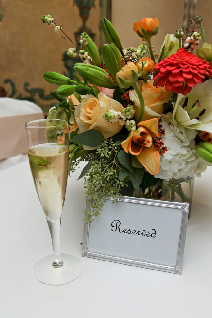 An elegant peach, green, and white bouquet with an eclectic mix of flowers. A single red flower spices up the color palette.
