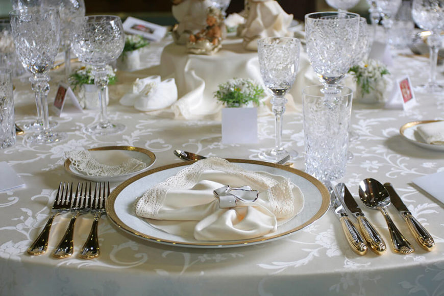 An absolutely delicate place setting on a white tablecloth. The silver rim of the plate is complemented by the silver trim of the ribbon on the lace-trimmed napkin.