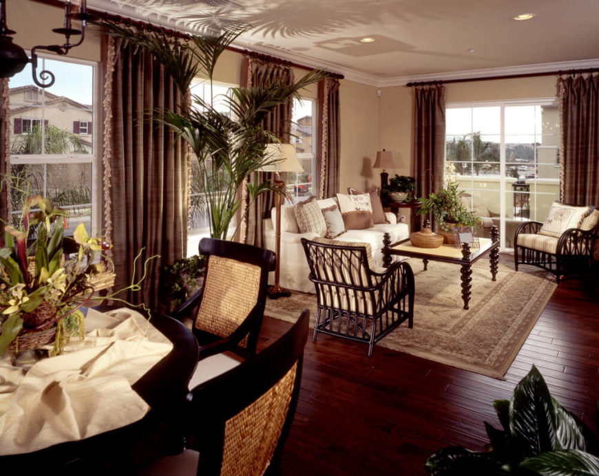 These dark hardwood floors have a rich red tone that pulls a rich wine color out of the thick fringed curtains on either side of each window. The dark wood is continued throughout the furniture.