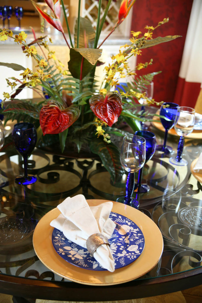 A table set for a semi-formal dinner on a wrought-iron glass-topped table. The dinner plate is in a bright gold, with a blue floral salad plate and a white napkin held together by a silver napkin ring. The stems of the wine glasses are in a deep blue.