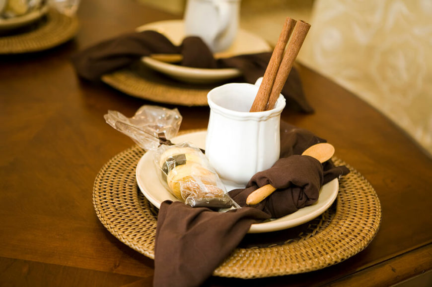A simple table setting for a cup of cocoa. The saucer rests in a wicker tray, and a small wooden spoon is wrapped in the dark brown napkin. On the side is a small cookie to dip.