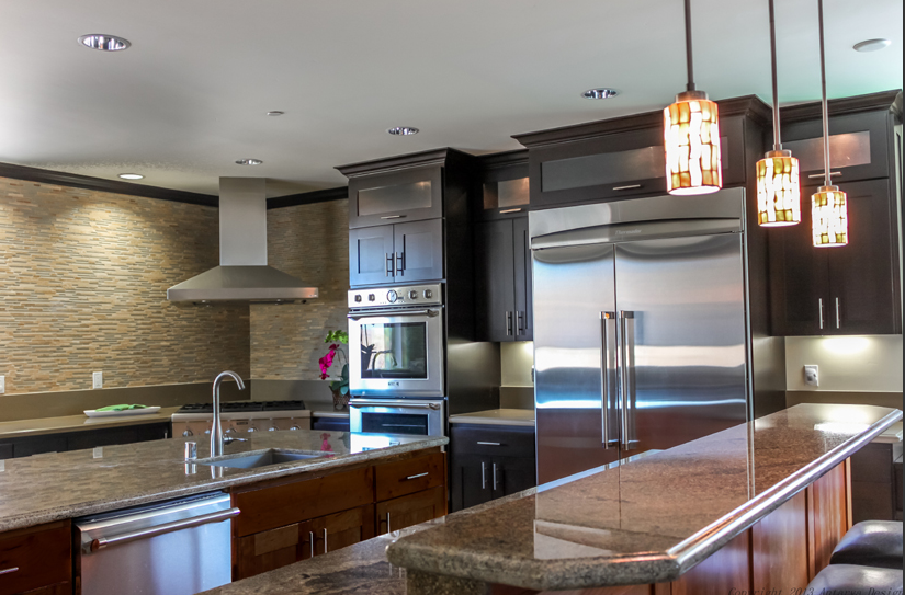 As we continue into the kitchen, we are met with an enormously functional space that includes two islands. One of the islands is strictly preparation area, while the other is split into two tiers and features an eat-in bar. The walls are tiled in a complementary backsplash. Jewel-like stained glass pendant lights hang above the eat-in bar.