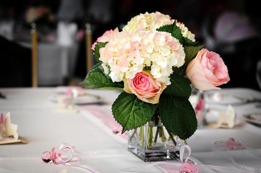 A beautiful floral arrangement of light pink roses and white hydrangeas with a soft touch of pink on the very tips of the petals. The flowers are suspended in a small, square glass vase.