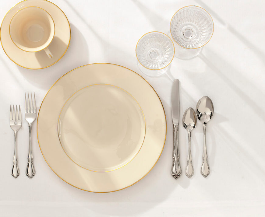 Without a placemat, a cream dish on a matte white table with perfectly polished silver is a simple, yet elegant setup.