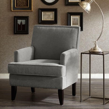 Here's another classically shaped club chair, this time in grey cloth upholstery with a nailhead trim. The angular shape makes it equally at home in a modern or traditional room setup.
