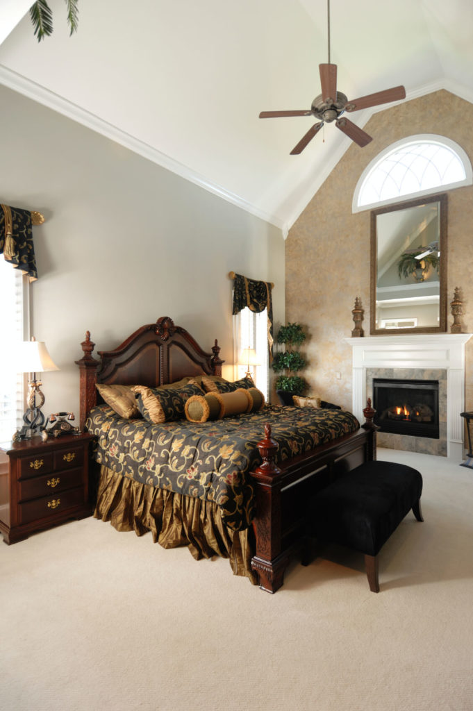 A more traditional bedroom in beige with contrasting dark wood furniture and rich texture in the bedding. Hanging from the center of the cathedral ceilings is a large fan.