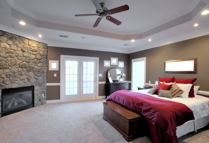 A luxurious primary bedroom with soft carpet, French doors to a patio, a custom tray ceiling, and a beautiful enclosed gas-burning fireplace in a stone accent wall. The walls themselves are a light grayish brown with a white chair rail running the perimeter of the room.