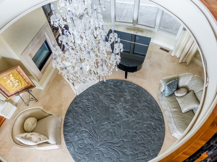 This view from the second floor landing shows the less grand, but no less beautiful chandelier that hangs above the living room, but also allows us to see the room's furniture more clearly. To the left is an enclosed gas-burning fireplace.