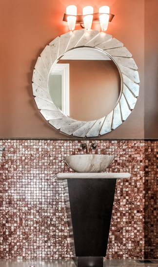 The downstairs powder room consists of bronze glass mosaic tiles along the bottom of the room, topped by light brown matte walls. A simple tapered pedestal sink is topped by a large metallic mirror.