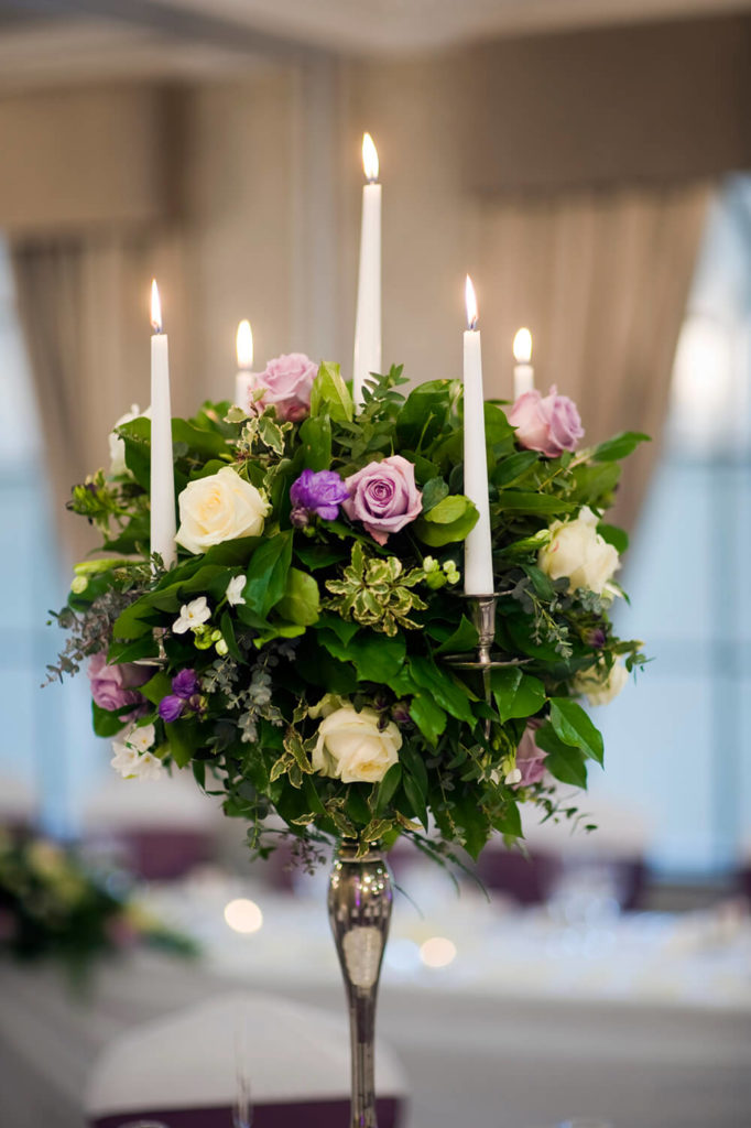 A romantic and elegant bouquet of greens and roses in white and lavender roses. Tall pillar candles rest in the metallic candle holders on four sides and in the center of the bouquet.