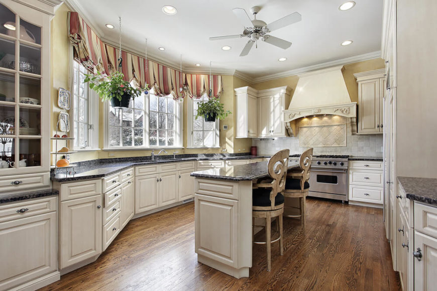 Marvelous English styled windows here are paired with beautiful roman curtains in this dazzling kitchen. The dark natural hardwood flooring has the perfect contrast with the cream colored cabinets.