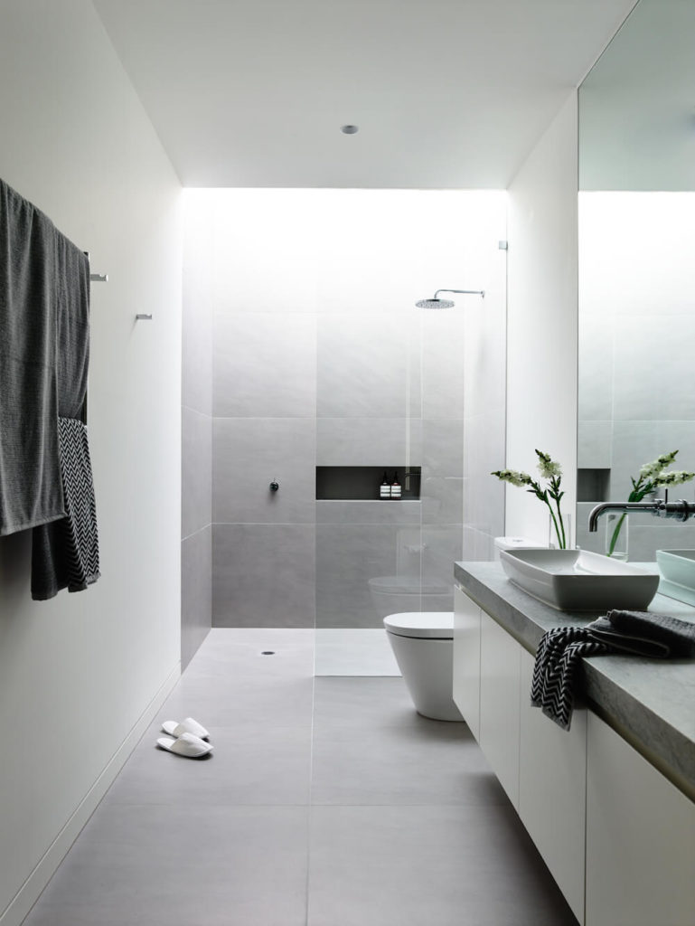 Viewed in a different light, the tile seems to turn light gray. At the opposite end from the soaking tub is a large glass shower enclosure and the commode.