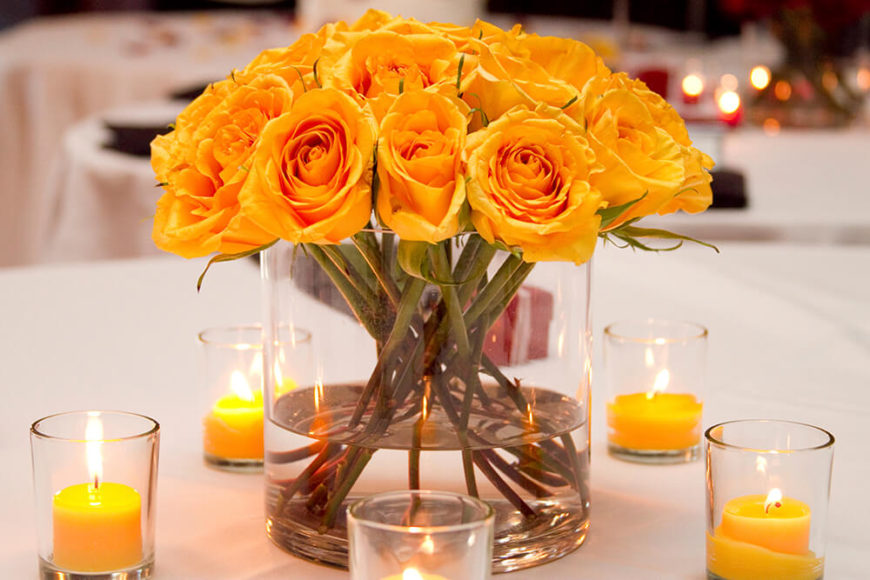 This floral centerpiece consists of beautiful bright yellow roses in a wide glass vase. The blooms rest neatly on the rim of the vase, creating a dome of petals. The vase is surrounded by small votive candles