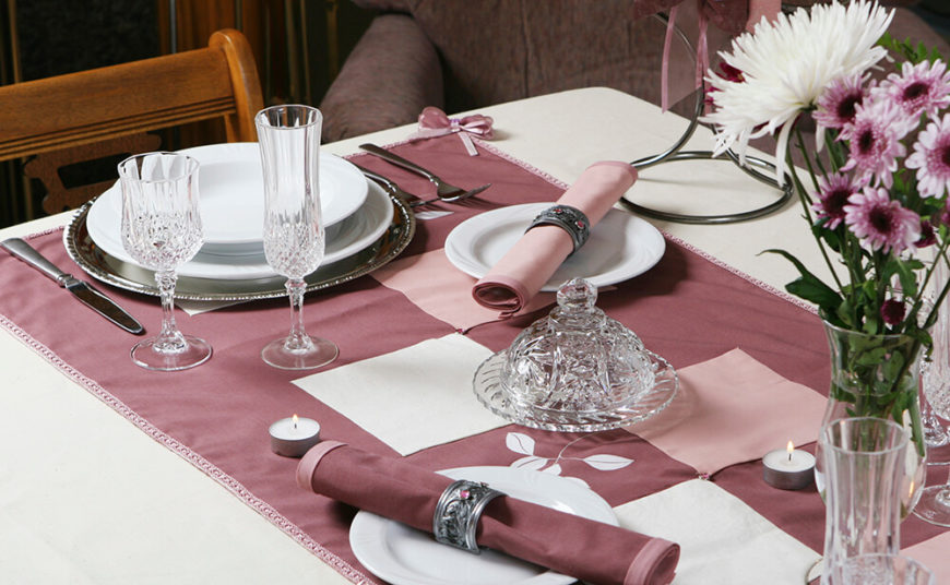 A fiercely elegant table setting in mauve with crystal ware glasses and jeweled silver napkin rings. The dinner plate is set into a larger silver plate, with a soup bowl at the center.