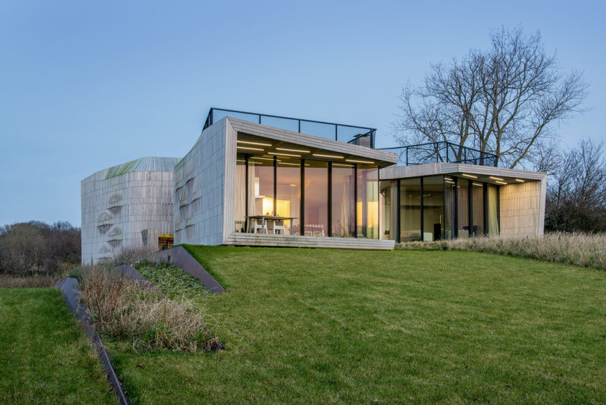 A final view of the exterior of this gorgeous home, showing two of the front wings of the home. We can also see the way the home is built into the naturally occurring landscape.