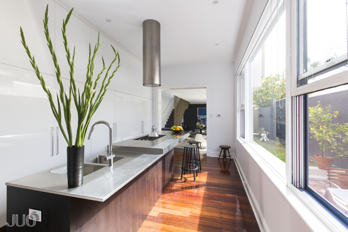 The sleekly modern kitchen centers on a lengthy island with stainless steel countertop. With a built-in sink, range, and dining space, the island shoulders most of the function, while sleek white cabinetry hides everything else in the room.