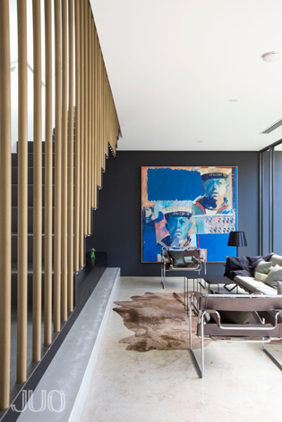 Viewed in the opposite direction, we see the white marble flooring contrasting with the charcoal toned walls. An elegant set of low profile modern furniture centers around another animal skin rug beneath a bold pop-art painting.