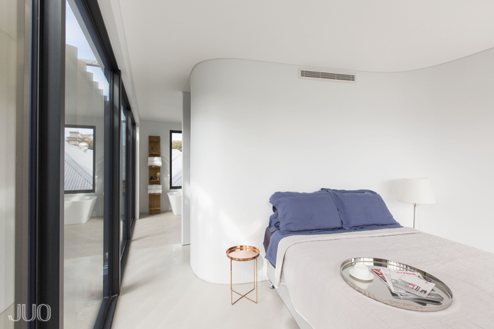 The primary bedroom is awash in bright white tones, with sensuously curved walls and sleek flooring. Full height glazing is shaded by the set of aluminum louvers, at left.