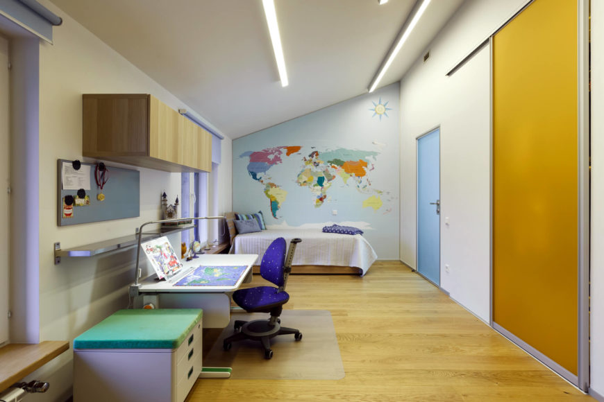 The children's room is fun and colorful. With a blue door, a world map, and a galaxy colored chair at the desk, this room is a dream for any child. This remarkable bedroom provides plenty of space for play and learning.