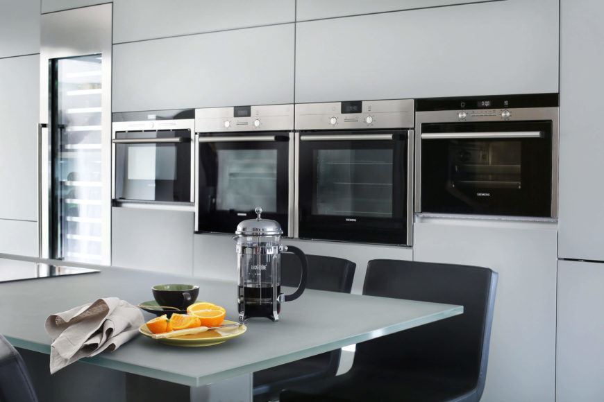Moving into the kitchen itself, we get a close view of the breakfast bar space on the large island. Smoked glass makes for an excellent partner to the sleek metallic tones surrounding, while black chairs and appliance faces add depth and contrast.