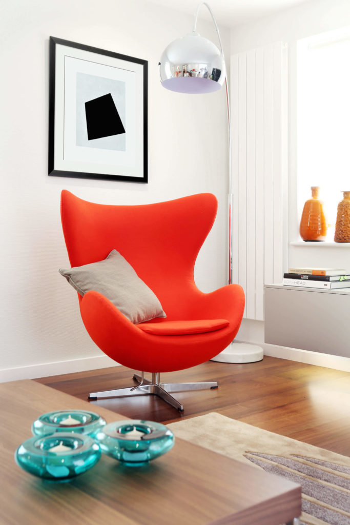 The bright and bold orange chair, in a uniquely modern egg shape, adds immense contrast and appeal, especially combined with the chrome overhead floor lamp. Embedded lighting in the cabinetry spills over the hardwood floor.