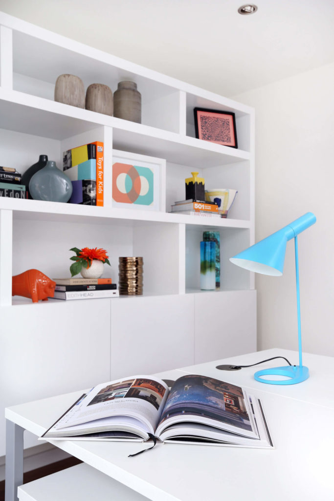 The study is highlighted by pristine white shelving and tabletops over dark hardwood flooring. The glossy and minimalist style eliminates any hint of clutter, making for a refreshingly open room.