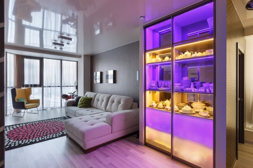 Immediately after the small entrance hallway is the living room, which features a comfy sectional sofa and a lighted display case in orange and purple.