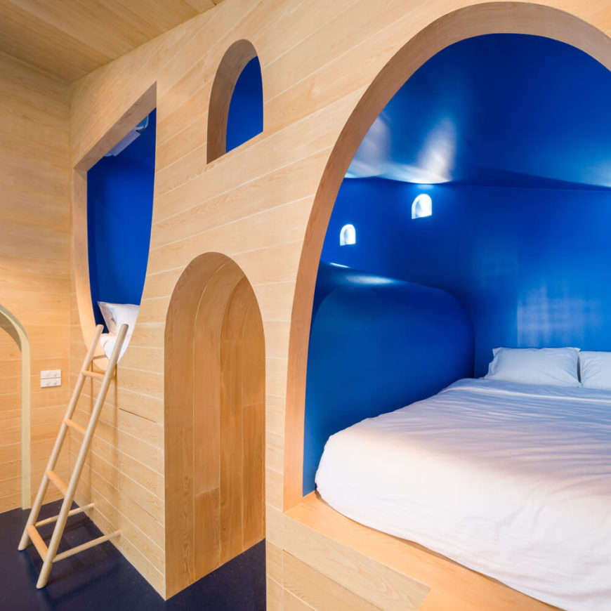 The bright blue hues in this room contrast with rich natural wood. Here we see the varied-elevation beds set into wall coves, with a tunnel-like hallway between.