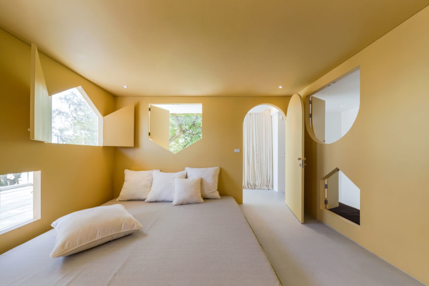 Mustard yellow primary bedroom showcases various shaped windows and an arched door. It has a gray floor bed accented with white pillows.