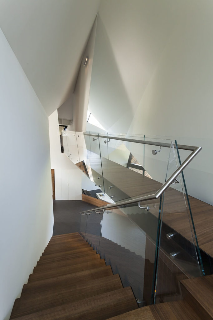 Here we see the set of stairs complete with a stainless steel railing and glass panels that leads up to the bridge connecting the primary suite and the study.