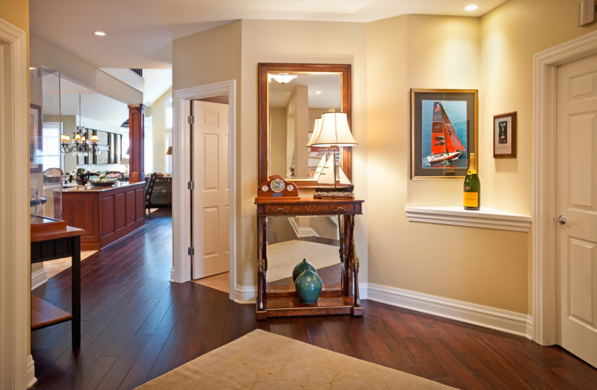 The open-plan space flows into this hallway, equipped with a plethora of detail, including display tables and art hung on the walls. Pristine white molding and doors highlight the warm and bright visual presence.