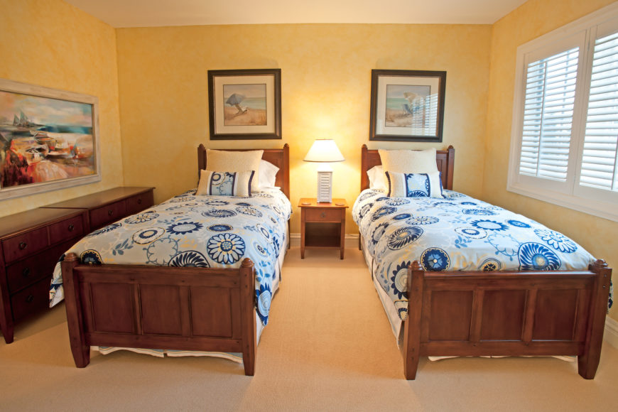 The guest bedroom features a warmer look, with soft yellow walls and rich wood pair of bed frames. White trim and beige carpet help lighten the look, while white and blue patterned bedding adds a burst of contrast and color.