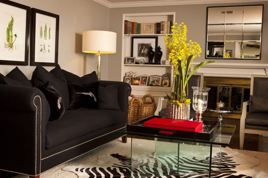 On this end of the room, we see an array of darker hued furniture, centered on an all-glass coffee table. The high contrast space includes lighter toned walls and rich, dark hardwood flooring.